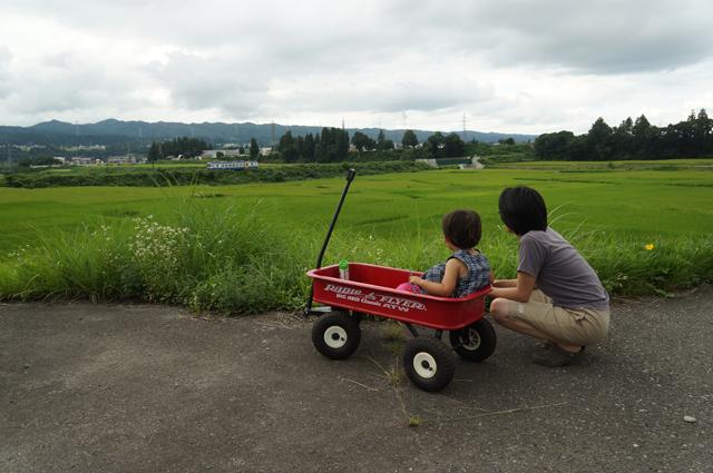 羽根川鉄橋を通過した飯山線色のキハ110を眺める家族