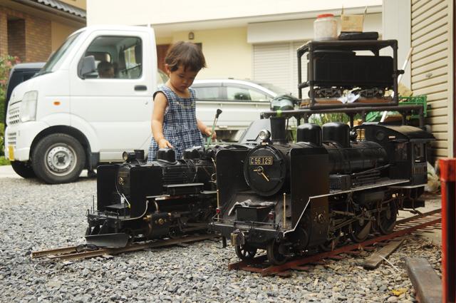 小さな汽車を磨く小さな子供