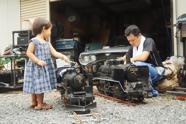 小さな汽車を磨く親子
