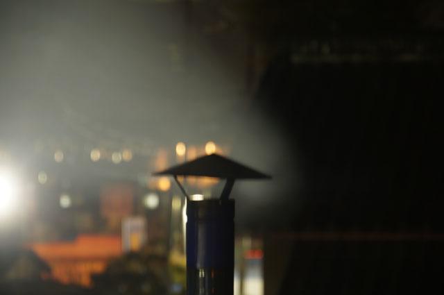 陣笠煙突から吐き出される煙 街路灯に照らされて