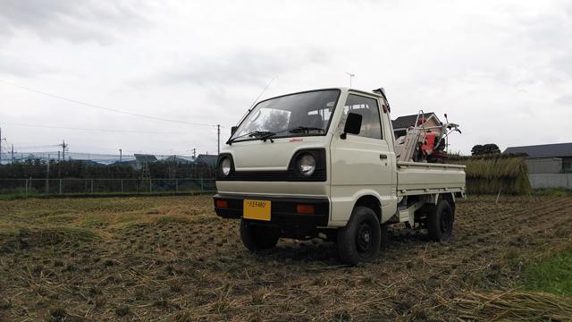 2スト3気筒4WDのST31、田んぼの中で稲刈機を積む