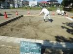 砂場表層をレーキで掻き集める